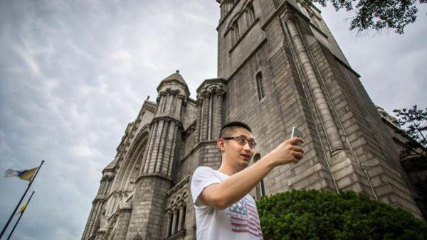 Jovem procura Pokemons em frente à Igreja nos EUA./ Foto: Catholic Herald.