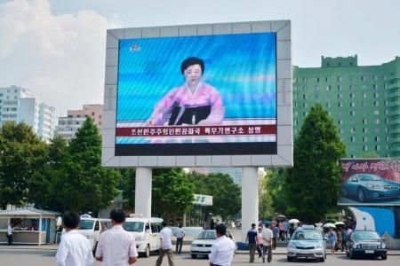 Norte-coreanos , em Pyongyang, caminham perto de uma tela gigante durante transmissão do anúncio do governo de que a Coreia do Norte realizou o seu quinto teste nuclear 9/09/ 2016. Crédito obrigatório para Kyodo/via REUTERS .
