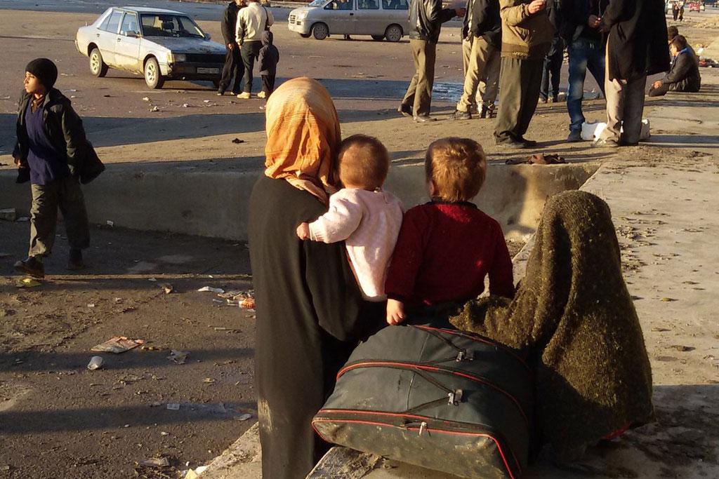 Uma mulher e seus filhos aguardam transporte em Alepo, na Síria / Foto: ONU - OCHA / L. Tom