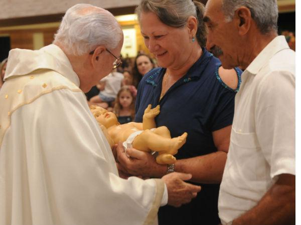 Monsenhor Jonas recebe imagem do Menino Jesus pelas de um casal. Foto: Micaelly Medeiros/cancaonova.com